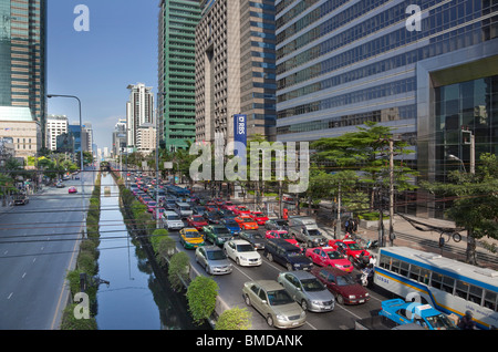 Sathon Road in central Bangkok. Mid afternoon traffic is queuing on the westbound side. - Stock Photo