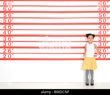 Girl in high heels by growth chart - Stock Photo
