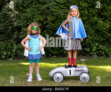 Young girls in capes playing dress up - Stock Photo