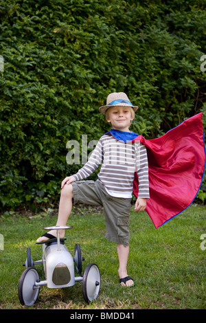 Boy in cape with toy car - Stock Photo