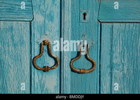 Rustic Blue Door Knockers - Stock Photo