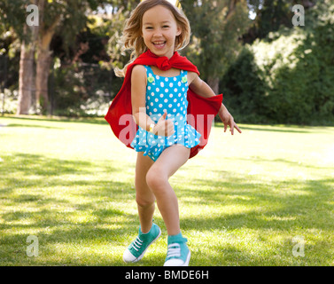 Girl in polka dot bathing suit and red cape running - Stock Photo