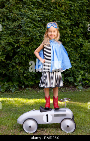 Girl with blue cape standing on toy car - Stock Photo