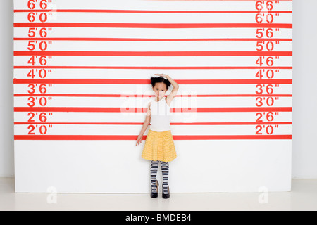 Girl in high heels measuring herself in front of growth chart - Stock Photo