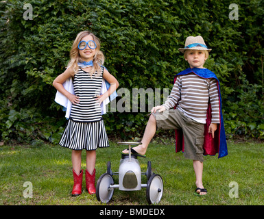 Boy and girl in capes with toy car - Stock Photo