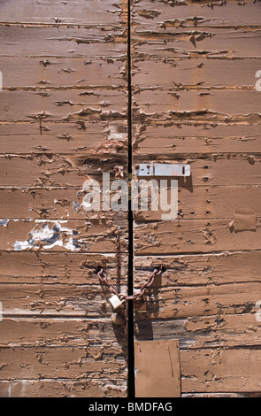 Detail of a padlocked, old weathered door with peeling paint in Encino, New Mexico. - Stock Photo