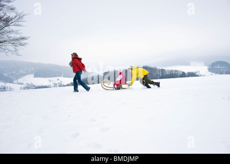 Mother Pulling Daughter in Sled, Son Pushing Sled from Behind - Stock Photo