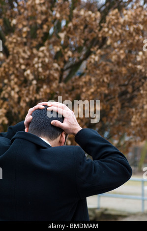 Rear view of a Middle Eastern businessman head in hands Berlin Germany - Stock Photo