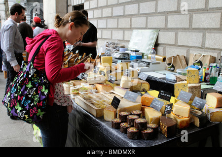 Young woman selecting cheeses from a farmers market cheese stall out side The Bank of Ireland Dublin Ireland - Stock Photo