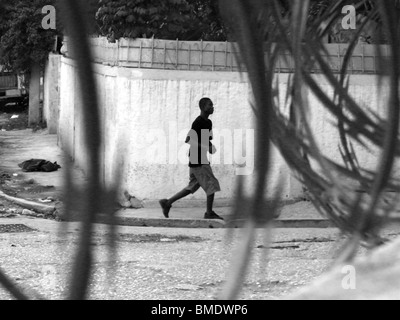 A man walks along a street in Port au Prince, Haiti, behind coils of razor wire - Stock Photo