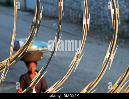 A woman carries a basket down a street in Port au Prince, Haiti, behind coils of razor wire - Stock Photo