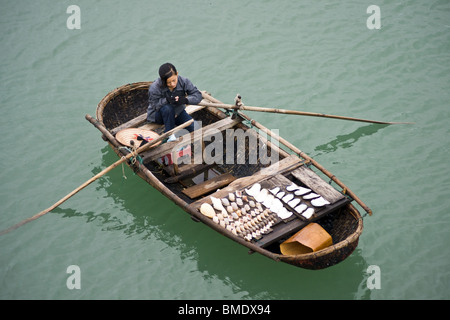 Young girl selling shells from rowing boat in Halong Bay, Vietnam - Stock Photo
