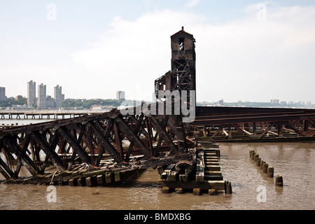 charred timber & rusted steel frame of burned out railway pier formerly used to offload railroad cars transported - Stock Photo