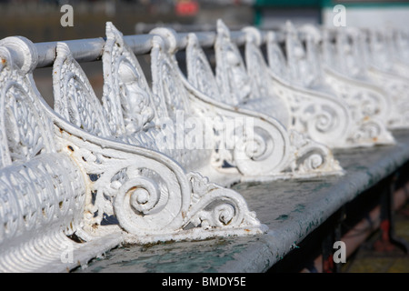 cast iron benches on an old victorian pier in the uk - Stock Photo