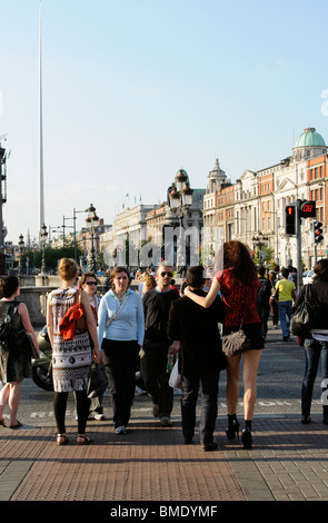 City centre Dublin Ireland pedestrians on O'Connell Bridge with a backdrop of O'Connell Street & The Spire - Stock Photo