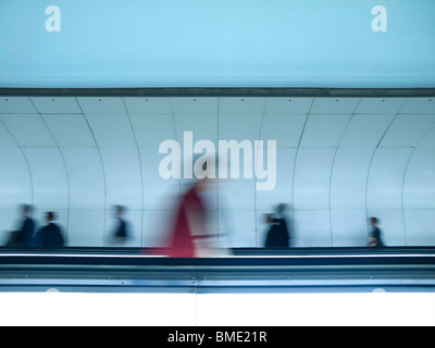 Blurred people walking towards differrent directions in a walkway tunnel. - Stock Photo