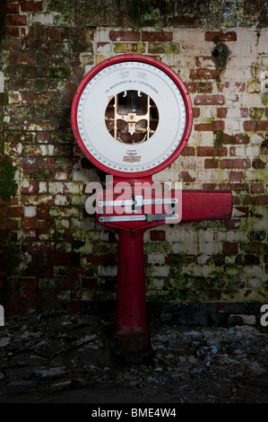 Disused Industrial Red Weighing Scales in the Store Loading Bay of a Derelict Lunatic Asylum. - Stock Photo