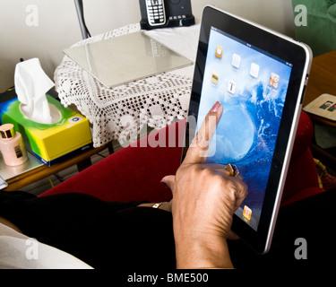 Asian woman using Apple iPad, TouchscreenTablet Computer, Book Reader, Digital Ebook, Modern, Logo, Brand, Luxury - Stock Photo