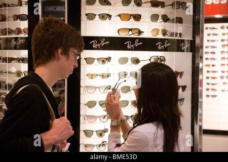A couple buying sunglasses, Terminal 3, Heathrow airport, London UK - Stock Photo