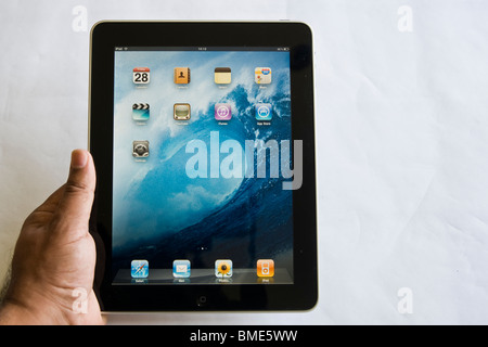 Man holding Apple iPad, TouchscreenTablet Computer, Book Reader, Digital Ebook, Modern, Brand, Luxury, screensaver, - Stock Photo
