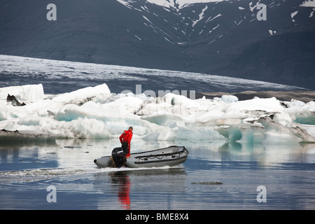 Man and dinghy in icy sea - Stock Photo