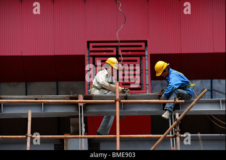 Two construction workers on the scaffold, China Pavilion, 2010 Shanghai World Expo Park, Pudong, Shanghai, China - Stock Photo