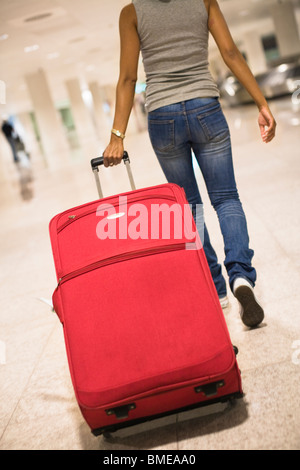 Woman with suitcase at an airport - Stock Photo