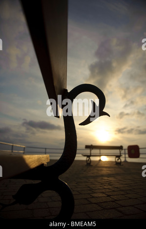 Silhouette of seaside benches at sunset, Aberystwyth Wales UK - Stock Photo