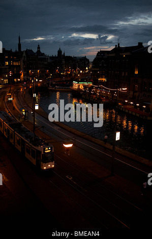 Tram in city along canal at night - Stock Photo
