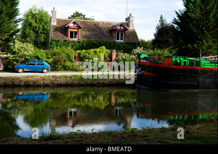 Reflection of house and car in pond - Stock Photo