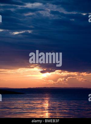 Scenic view of sun setting over sea - Stock Photo