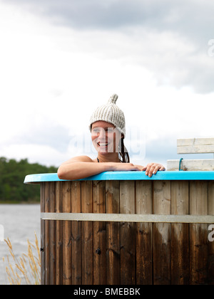 Woman bathing in tub by sea - Stock Photo