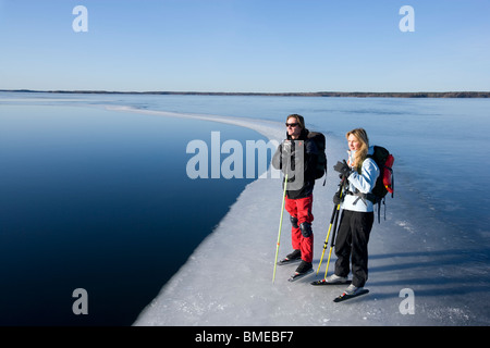 Two people standing near lake - Stock Photo