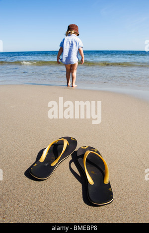 Flip flops on beach with boy in sea - Stock Photo