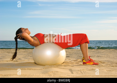 Woman exercising on beach with exercise ball - Stock Photo