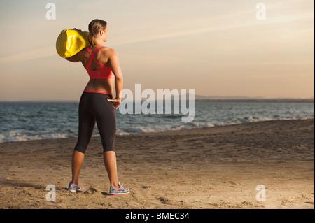 Woman exercising on beach - Stock Photo