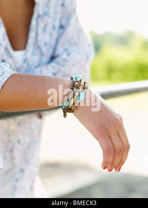 Woman leaning on railings wearing bracelet - Stock Photo