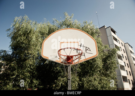 Basketball net in front of trees and buildings - Stock Photo