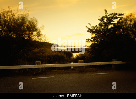 Road with view of river in background at dawn - Stock Photo