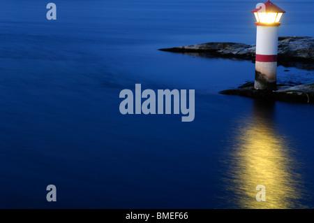 Scandinavia, Sweden, Vastkusten, View of illuminated lighthouse on sea, elevated view - Stock Photo