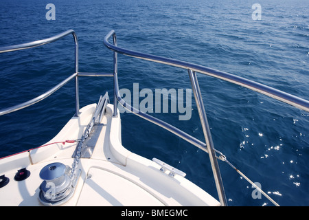 boat bow sailing on blue sea with anchor chain and winch detail - Stock Photo