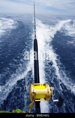 fishing big game rod and reel on boat wake prop wash - Stock Photo