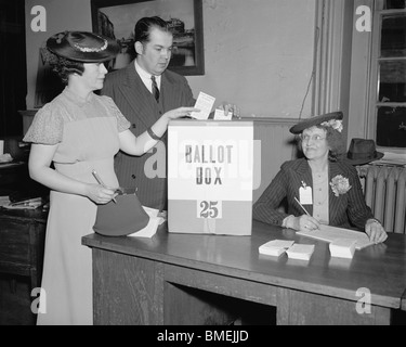 Vintage 1930s photo of a man and woman placing their votes in a ballot box in Washington DC as an election official - Stock Photo