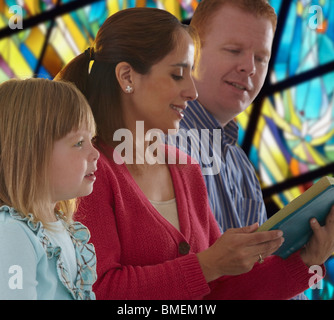 A Family Reading The Bible Together In Church - Stock Photo