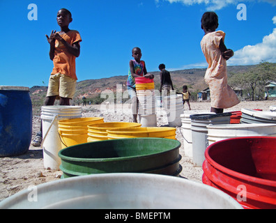 Children wait for water distribution by the United Nations in the dusty semi-desert outside Gonaives, Haiti - Stock Photo