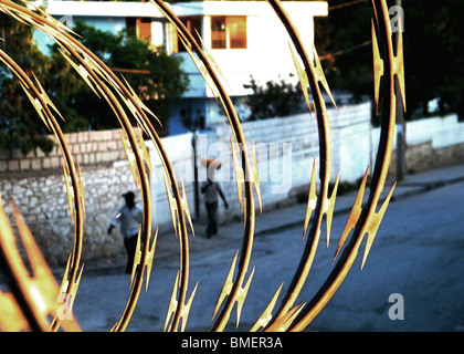 A street in Port au Prince, behind coils of razor wire in the early morning, Haiti - Stock Photo
