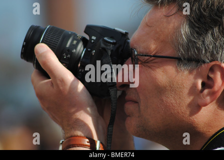 A man wearing glasses takes a photo with a digital slr camera, Venice, Italy - Stock Photo