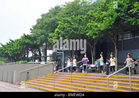 Filipino maids, dancing with glasses on heads and in hands, trees above promenade steps along the Central Waterfront, - Stock Photo