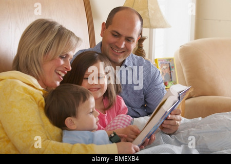 A Mother And Father Reading With Their Children At Bedtime - Stock Photo