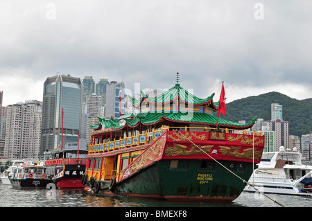 Gold stern of Chinese 'Phoenix Water Tour Boat', moored in Causeway Bay Typhoon Shelter, looking towards skyscrapers, - Stock Photo